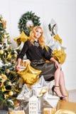 Muchacha que se sienta al lado del árbol de navidad y de presentes Imagen de archivo