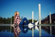 Muchacha que se sienta al lado del agua con la reflexión de su uno mismo Foto de archivo libre de regalías
