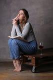 Muchacha que se sienta a bordo con el vidrio de vino Fondo gris Fotos de archivo libres de regalías