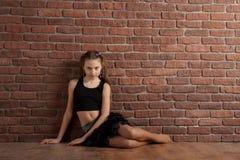 Muchacha que se sienta cerca de la pared de ladrillo Imagen de archivo libre de regalías