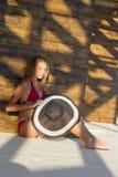 Muchacha que se sienta cerca de la pared de madera Fotos de archivo