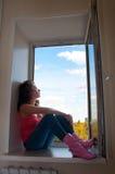 Muchacha que se sienta cerca de la ventana abierta Imagen de archivo