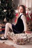 Muchacha que se sienta cerca de las decoraciones del Año Nuevo Imagen de archivo