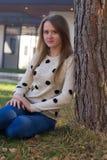 Muchacha que se sienta cerca de un árbol Foto de archivo