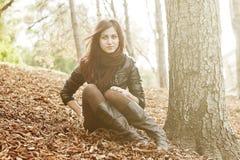 Muchacha que se sienta cerca de un árbol en un parque Fotos de archivo libres de regalías