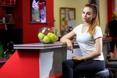 Muchacha que se sienta cerca de un cuenco de manzanas en un gimnasio fotos de archivo libres de regalías