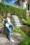 Muchacha que se sienta cerca de una cascada en un parque Imágenes de archivo libres de regalías
