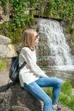 Muchacha que se sienta cerca de una cascada en un parque Fotos de archivo