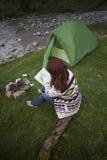 Muchacha que se sienta cerca de una hoguera Foto de archivo libre de regalías