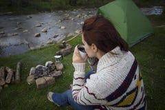 Muchacha que se sienta cerca de una hoguera Foto de archivo