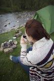 Muchacha que se sienta cerca de una hoguera en el sitio para acampar que mira el mapa y que bebe el café Fotografía de archivo libre de regalías