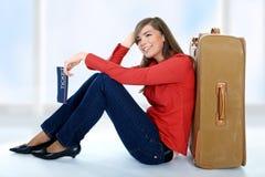 Muchacha que se sienta cerca de una maleta Fotografía de archivo libre de regalías