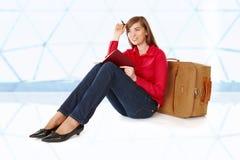 Muchacha que se sienta cerca de una maleta imagenes de archivo