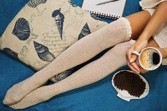 Muchacha que se sienta con el coffe y las galletas en la cama que planea su día Foto de archivo