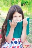 Muchacha que se sienta con el libro en la hamaca al aire libre Imagen de archivo libre de regalías