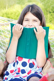 Muchacha que se sienta con el libro en la hamaca al aire libre Imagen de archivo