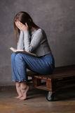 Muchacha que se sienta con el libro que cubre su cara Fondo gris Imagen de archivo