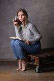 Muchacha que se sienta con el libro y el vidrio de vino Fondo gris Foto de archivo libre de regalías
