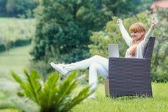 Muchacha que se sienta con el ordenador portátil Foto de archivo
