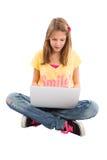 Muchacha que se sienta con el ordenador portátil aislado en blanco Fotos de archivo