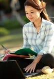 Muchacha que se sienta con el ordenador portátil y los libros Imagen de archivo libre de regalías