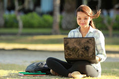 Muchacha que se sienta con el ordenador portátil y los libros Foto de archivo