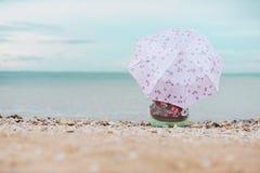 Muchacha que se sienta con el paraguas en la orilla de mar Foto de archivo libre de regalías