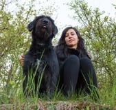 Muchacha que se sienta con el perro en prado Imagenes de archivo