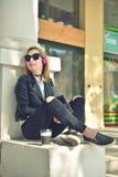 Muchacha que se sienta con la almohadilla táctil Imagenes de archivo