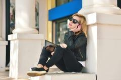 Muchacha que se sienta con la almohadilla táctil Fotos de archivo libres de regalías