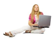 Muchacha que se sienta con la computadora portátil Foto de archivo libre de regalías