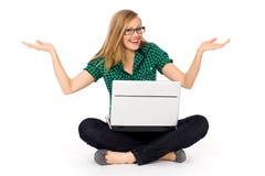 Muchacha que se sienta con la computadora portátil Fotografía de archivo libre de regalías