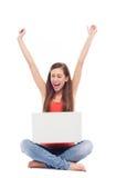 Muchacha que se sienta con la computadora portátil, brazos levantados Imagen de archivo