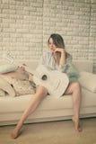 Muchacha que se sienta con la guitarra Fotos de archivo libres de regalías