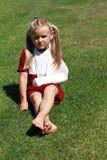 Muchacha que se sienta con la mano quebrada Imagen de archivo