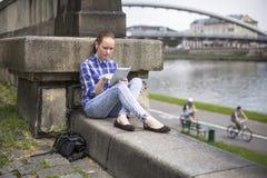 muchacha que se sienta con la tableta al aire libre en la ciudad cerca del río Fotos de archivo libres de regalías