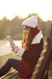 Muchacha que se sienta con la tableta en banco en parque Foto de archivo libre de regalías