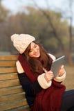 Muchacha que se sienta con la tableta en banco en parque Imagenes de archivo