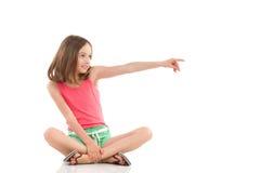 Muchacha que se sienta con las piernas cruzadas y señalar Imagenes de archivo