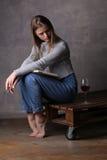 Muchacha que se sienta con los brazos cruzados Fondo gris Foto de archivo libre de regalías
