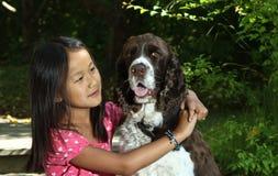 Muchacha que se sienta con su perro Imagenes de archivo