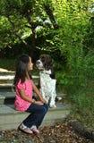 Muchacha que se sienta con su perro Foto de archivo