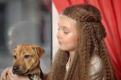 Muchacha que se sienta con un perrito en sus brazos Imagenes de archivo