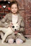 Muchacha que se sienta con un perrito en sus brazos Imágenes de archivo libres de regalías