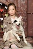 Muchacha que se sienta con un perrito en sus brazos Fotografía de archivo
