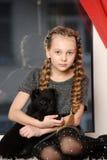 Muchacha que se sienta con un perrito en sus brazos Fotos de archivo