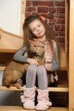 Muchacha que se sienta con un perrito en sus brazos Foto de archivo libre de regalías