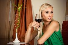 Muchacha que se sienta con un vidrio de vino Imágenes de archivo libres de regalías