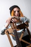 Muchacha que se sienta con una guitarra acústica foto de archivo libre de regalías