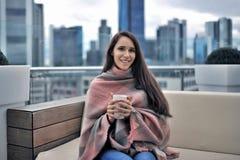 Muchacha que se sienta con una taza y una manta en un café en el tejado de un hig Foto de archivo